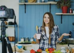 Young attractive woman recording video food blog about cooking on dslr camera in kitchen at home